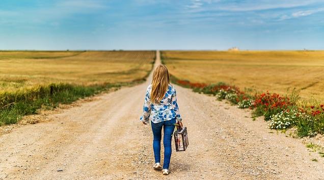 vrouw met koffer op landweg