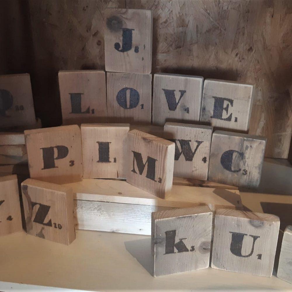 scrabble letters op houten bordjes